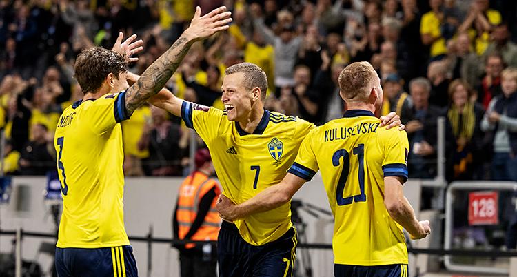 Från en match i fotboll. Viktor Claesson firar sitt mål med två andra spelare. De har gula tröjor. i bakgrunden syns publiken.
