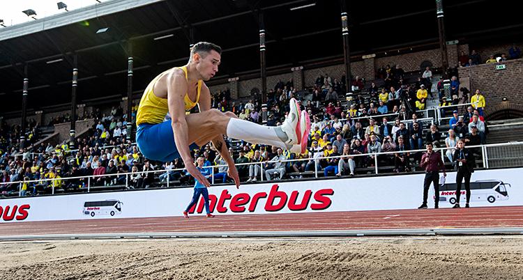 Han gör ett hopp i längdhopp. Han är i luften. Snart kommer han att landa i sanden.
