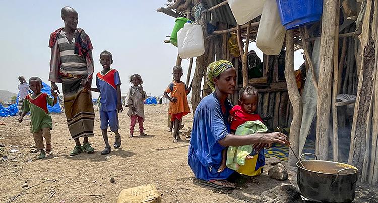 En kvinna sitter utomhus och lagar mat. Hon håller i ett litet barn. Bakom henne finns flera andra barn. En man håller två av barnen i handen.