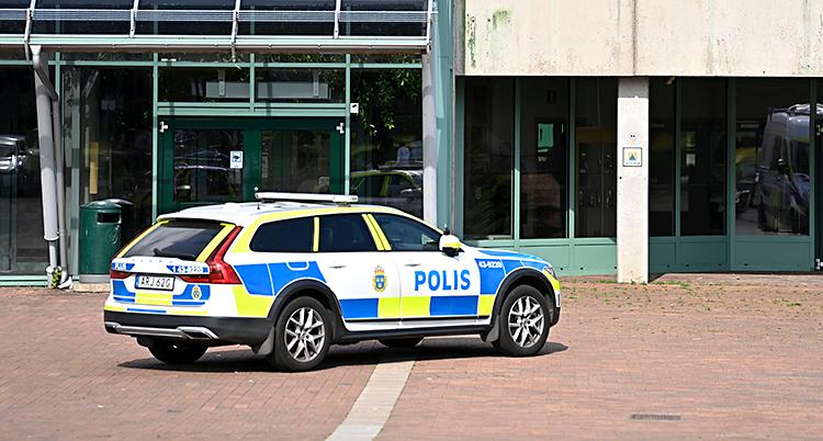 En polisbil står parkerad utanför en skola.