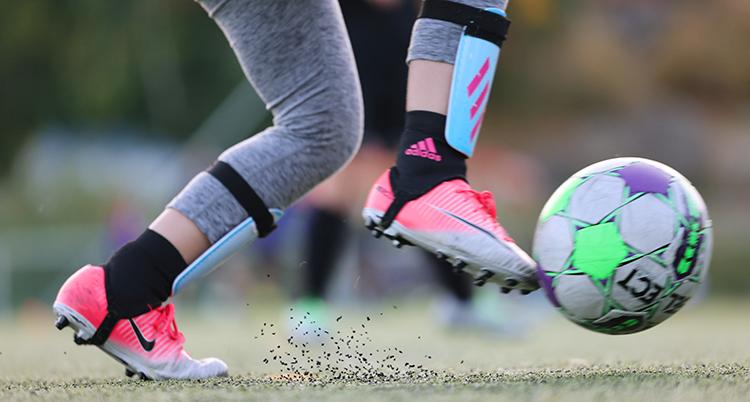 Ett barn spelar fotboll. Vi ser bara benen och en boll.