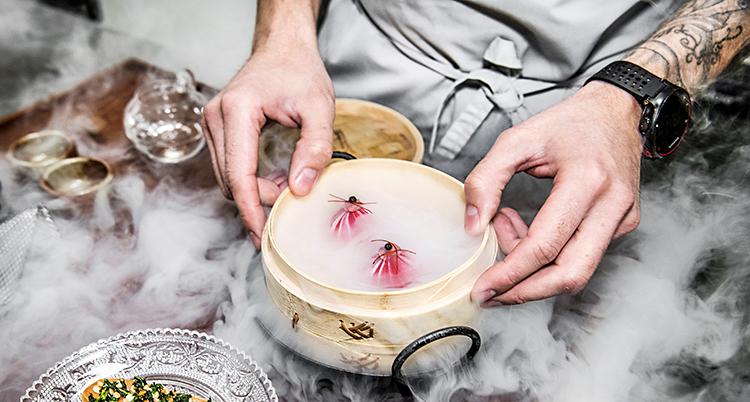 Kockens händer håller i en liten skål. Det ryker av kolsyreis från skålen.