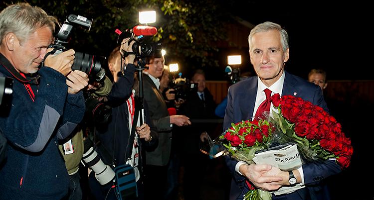 Han är utomhus och det är mörkt. Han har en massa rosor i famnen. Han blir fotograferad av många fotografer.