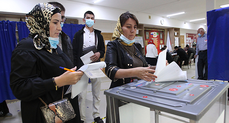 Två kvinnor håller på att rösta i valet.