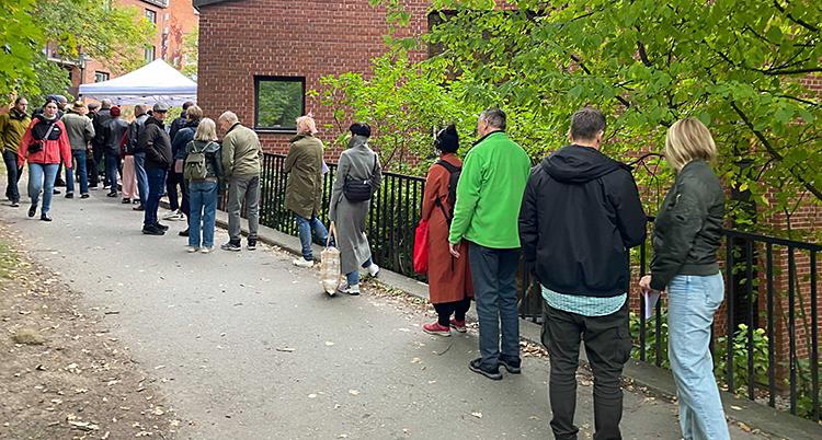 Människor står i kö utanför en kyrka.