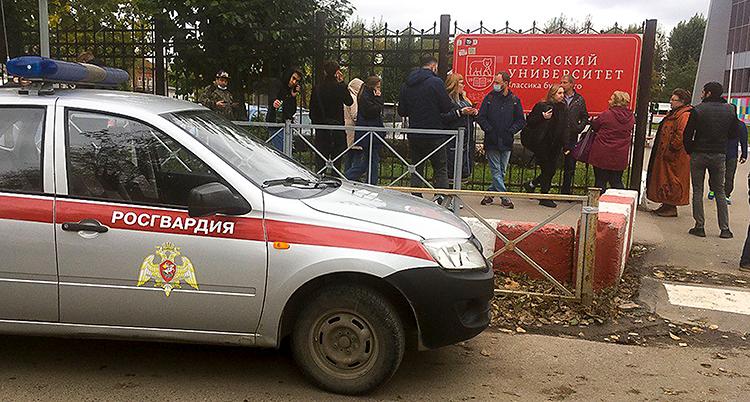 En grupp människor står vid ett staket. Framför dem finns en polisbil.