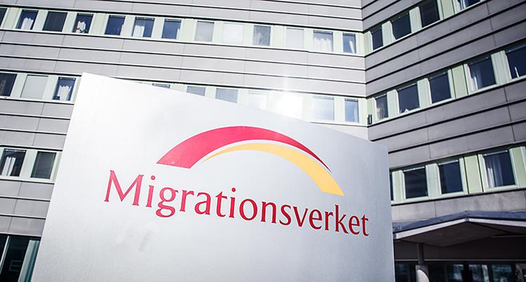 En skylt där det står Migrationsverket. Skylten står utanför ett stort hus.
