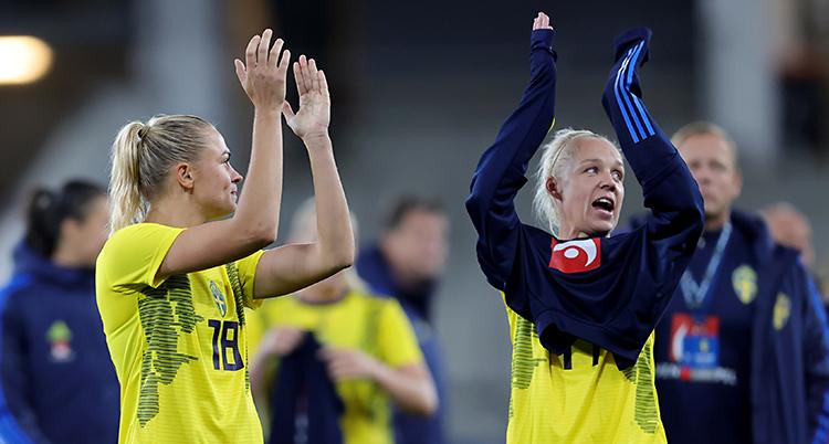 De står på fotbollsplanen och tackar publiken genom att klappa händerna.