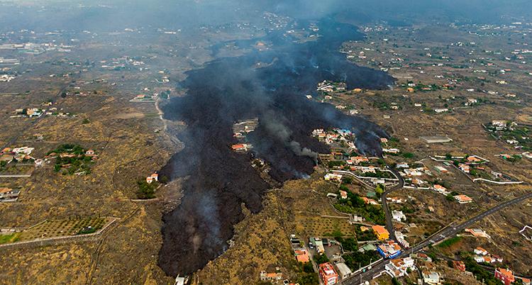 En bild från luften som visar hur svart lava flyter fram över gräs och hus.