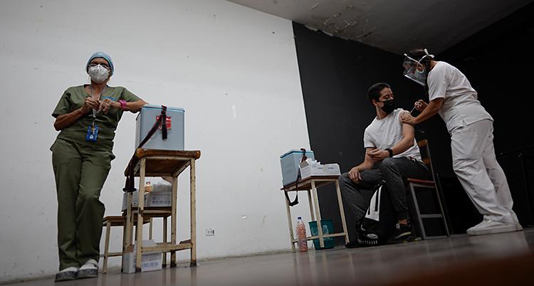 En man sitter ner på en stol. En person ger honom en spruta i armen.