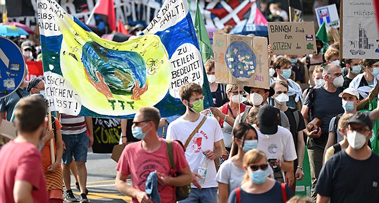 Människor går på en gata med plakat och banderoller. De har munskydd på sig.