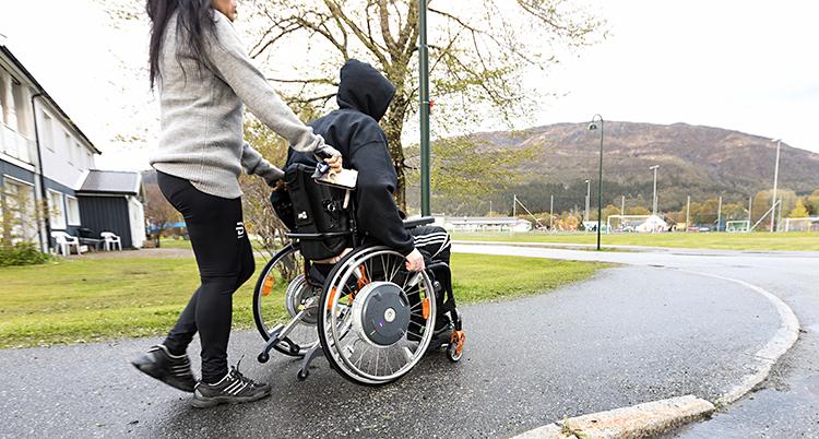 Bilden är tagen på en trottoar, utomhus. En person sitter i en rullstol. Bakom står en annan person och håller i rullstolen.