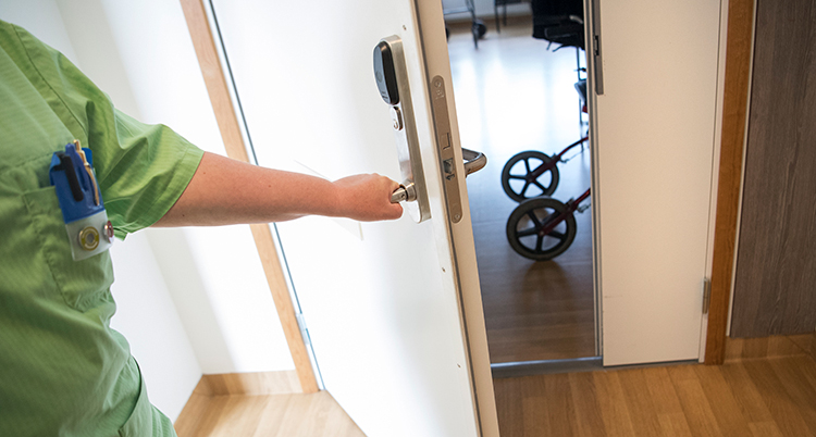 Sjuksköterska öppnar en dörr.