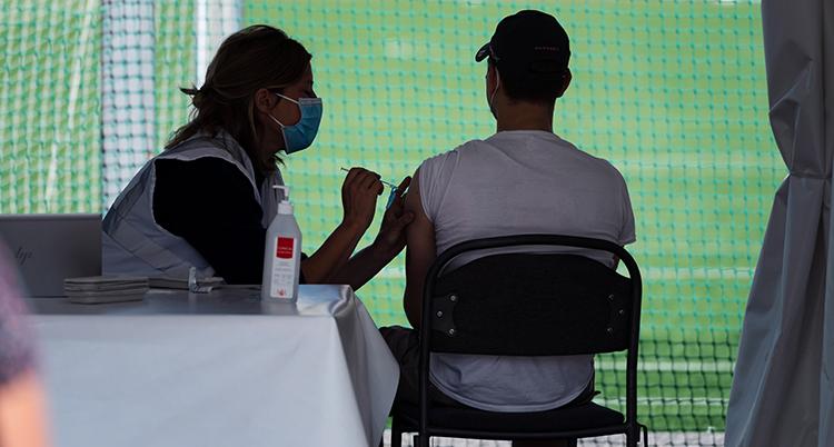 silhuetten av en ung man som får vaccin.