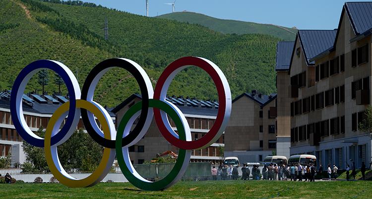 OS-ringarna är i förgrunden, på en gräsmatta. Bakom syns gröna berg och hus.
