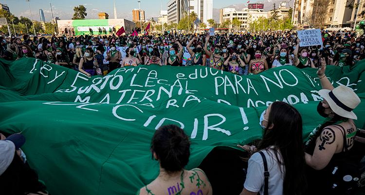 Många människor demonsterar på gatan och håller i en stor grön flagga med vit text