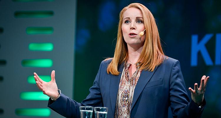 Hon står vid en mikrofon och talar. Hon gestikulerar med händerna. Håret är rödblont, kavajen är blå.