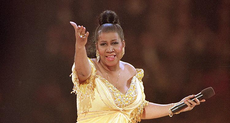 Hon har håret i en knut och en gul klänning på sig. Hon har en mikrofon i ena handen.