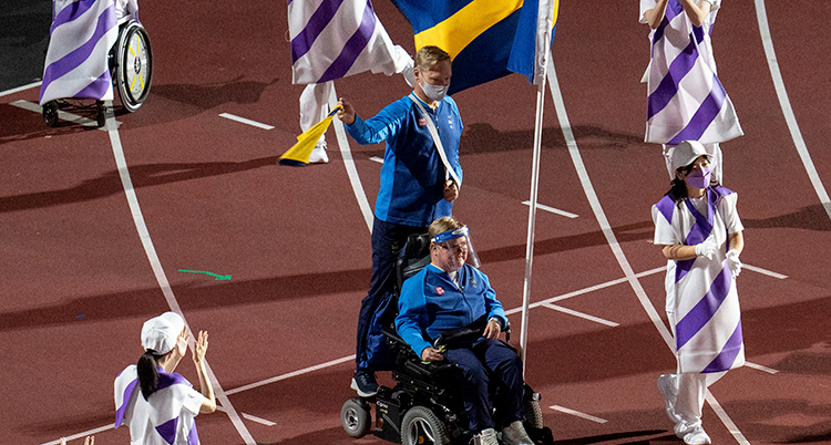 Han är i mitten av bilden, sitter i en rullstol och bär den svenska flaggan. Han har blå tröja. Han är på en arena.