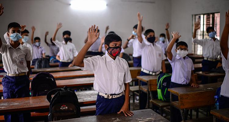Pojkar i vita skjortor står vid sina bänkar och räcker upp ena handen