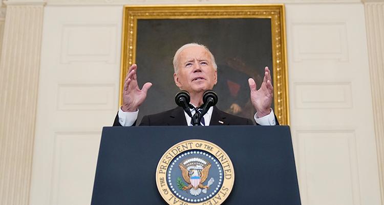 Biden i en talarstol. Han håller upp händerna.