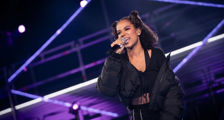 Hon håller i en mikrofon mot munnen. Hon har svarta kläder, mörkt hår och står på en scen med lila och ljus.