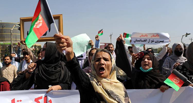 En kvinna i svart dräkt och beige huvudduk sträcker upp en flagga i luften. Bakom syns flera kvinnor som demonstrerar ute på gatan. De har banderoller.