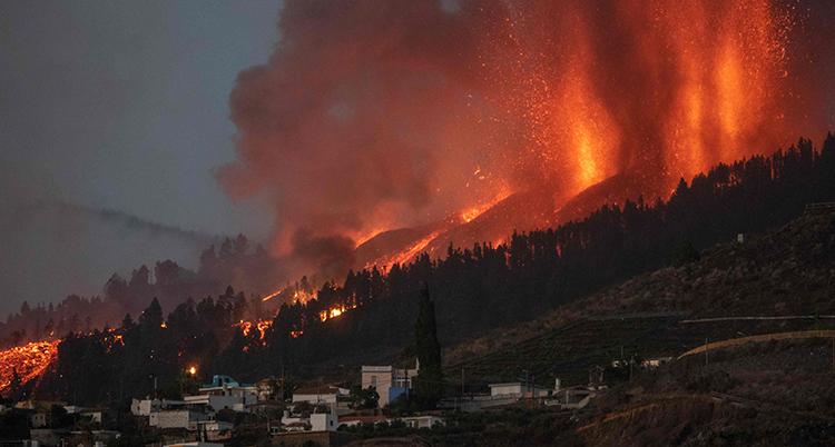 Rök och eld sprutar upp mot luften från marken vid vulkanutbrottet. På marken syns hus.