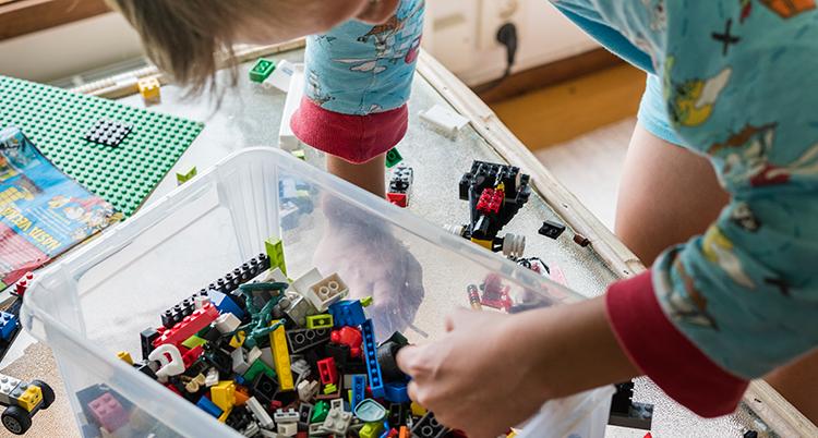 Barnet plockar med handen i en plastlåda med lego