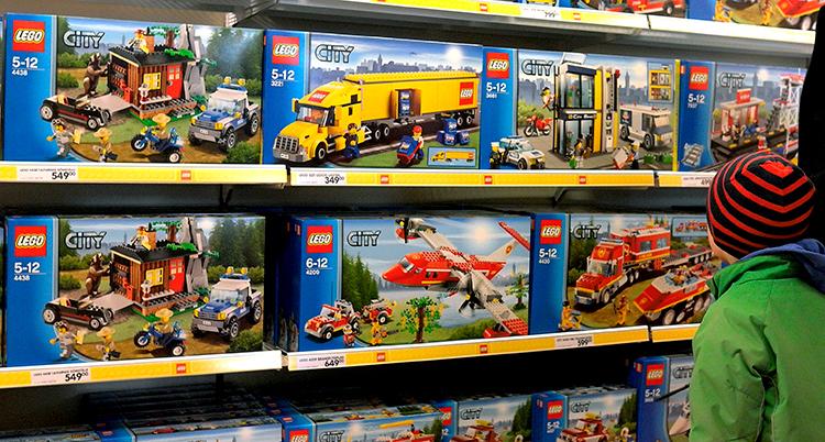 Ett barn tittar på hyllor med förpackningar med lego.