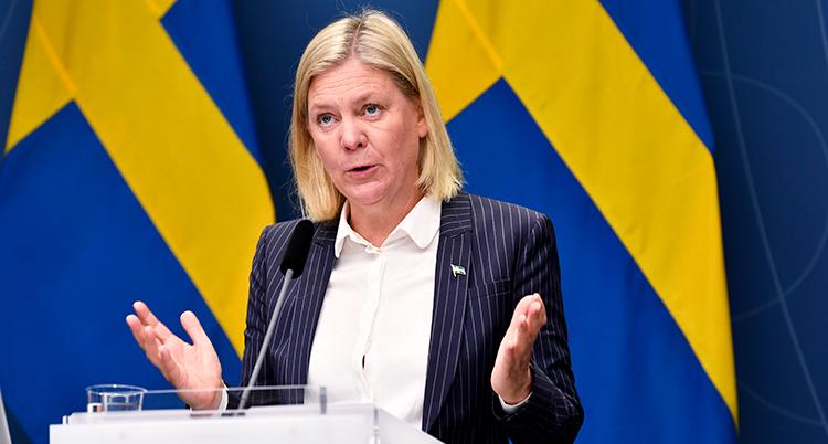 Hon talar i en mikrofon. Bakom henne syns Sveriges flagga.