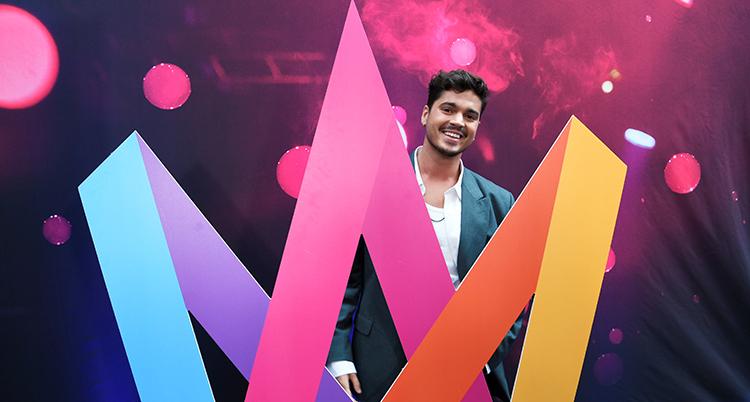 Han ler bakom den färgglada loggan för Melodifestivalen.