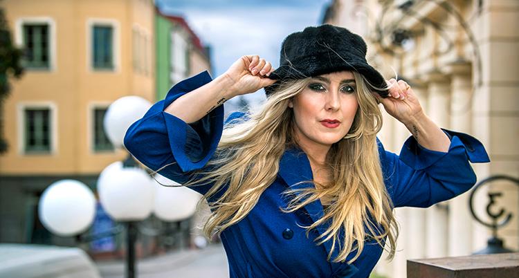 Hon har en svart hatt och blå kappa.