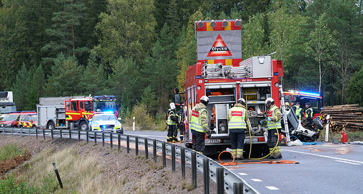 En bilväg där det står brandbilar och en polisbil.