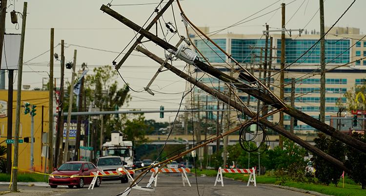 En stolpe för el har ramlat ner över en väg.