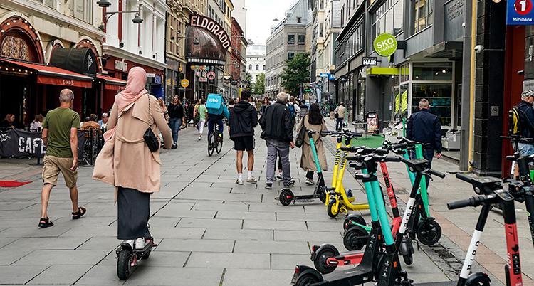 Folk går på gatan. En kvinna åker på en elsparkcykel.