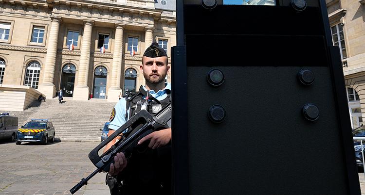 En polis står med ett stort vapen och vaktar framför domstolsbyggnaden.