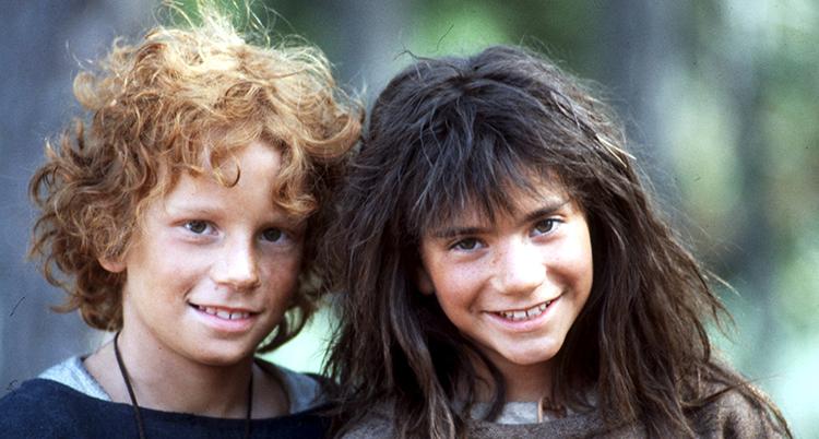 Två barn sitter nära varandra. Han har rött lockigt hå. Hon har mörkt tjockt långt hår.