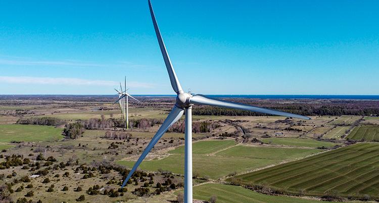Vindkraftverk som står i ett landskap.