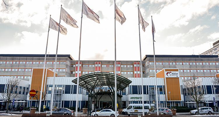 En gråorange byggnad mot en grå himmel. Vita flaggor vajar på flaggstänger i förgrunden, intill en parkering med bilar.