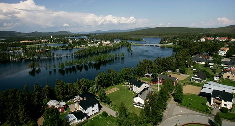 Staden ses från luften, med vy över älven och skogen.