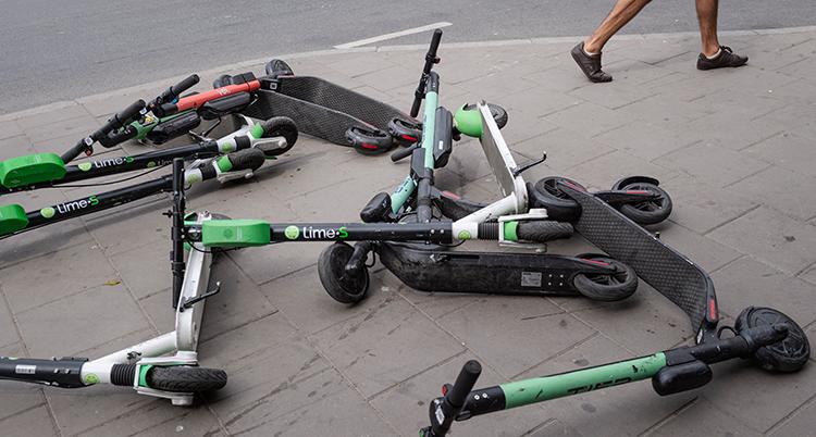 Sparkcyklar ligger på en trottoar