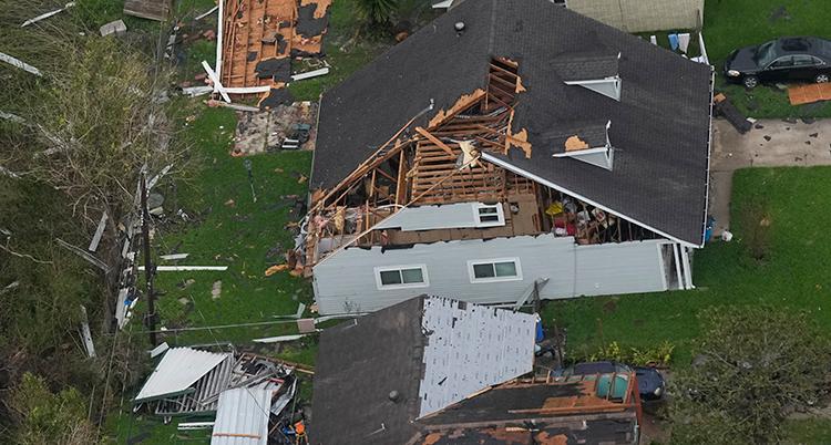 En flygbild på ett hus. Halva taket är borta. På marken ligger bråte