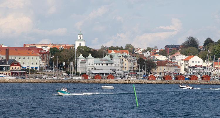 en båt kör i vattnet framför en stad med hus, träd och hamnbodar