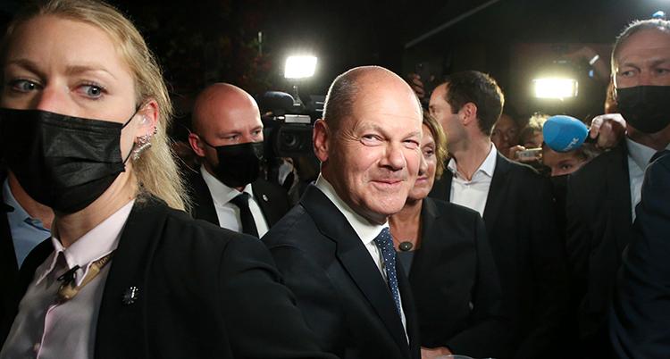 En politiker ler in i kameran.