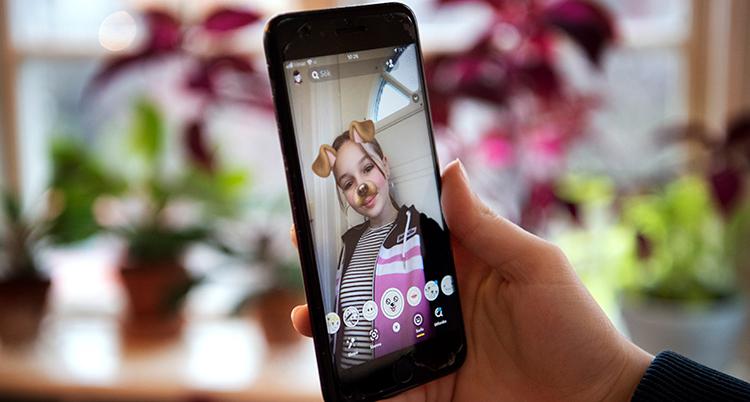 En hand håller i en mobil med en bild av en flicka. Bakom syns ett fönster med krukväxter.
