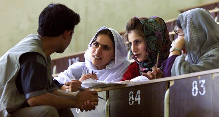 En man sitter framför tre kvinnor och pratar med dem. De jhar slöja men inte framför ansiktet.