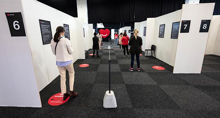 Röda markeringar syns på golvet. Det står en människa vid varje markering.