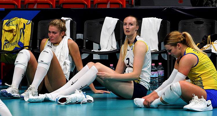 De tre kvinnorna har träningskläder, de sitter på golvet på en plan och ser deppiga ut.