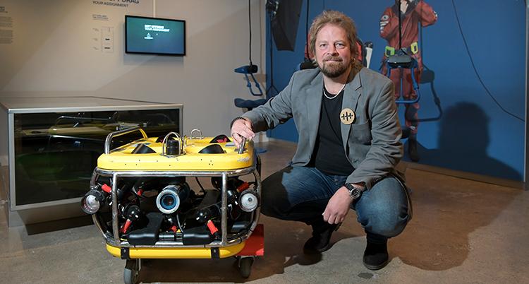 En man bredvid en gul apparat.